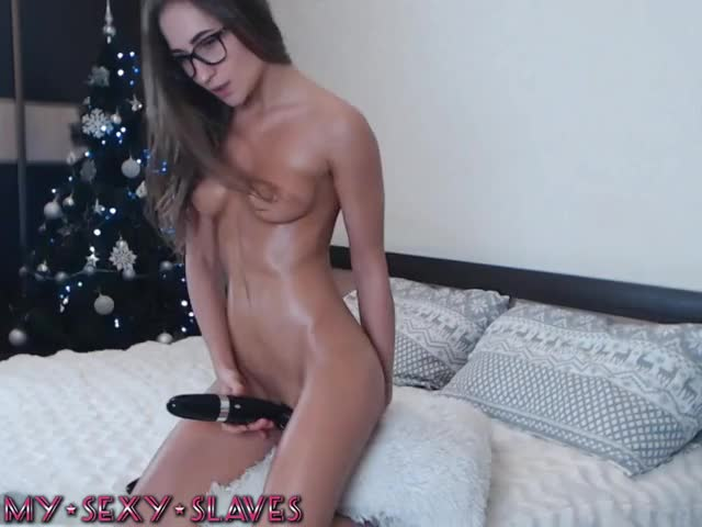 Oiled girl in glasses plays with vibrator