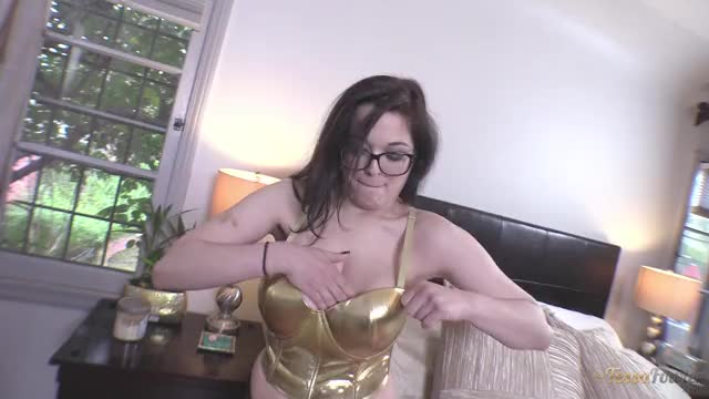 tessa Fowler bursting out of a gold corset